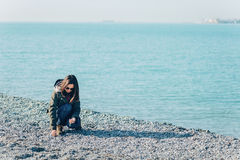 Young woman collects stones on coastline Stock Photos