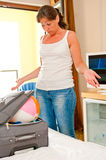Young woman collects things in a suitcase Stock Photography