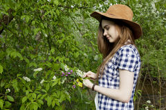 Young woman collects wild flowers in the forest. Young woman collects wild flowers in the wood Royalty Free Stock Photography