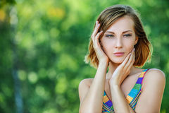 Young woman in color dress thought Stock Photography