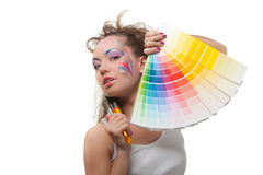 Young woman with a color guide and paintbrushes. Stock Photos