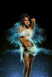 Young woman with colored powder exploding around her Royalty Free Stock Photo