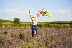 Young woman with colorful ballons on the lavander field Royalty Free Stock Photo