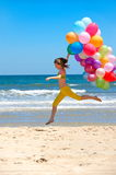 Young woman with colorful balloons on the beach Royalty Free Stock Photography