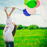 Young woman with colorful balloons in the field royalty free stock photography