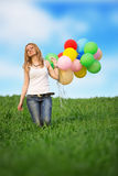 Young woman with colorful balloons on a green meadow Stock Photography
