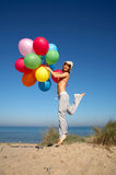 Young woman with colorful balloons jumping. Young woman with a bunch of different colored balloons jumping on the beach Stock Photography