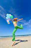 Young woman with colorful balloons jumping Royalty Free Stock Photography