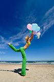 Young woman with colorful balloons jumping Stock Images