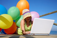 Young woman with colorful balloons and laptop Stock Photography