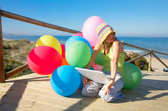 Young woman with colorful balloons and laptop Royalty Free Stock Image