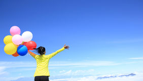 Young woman with colorful balloons on mountain peak Royalty Free Stock Image