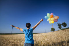 Young woman with colorful balloons in summer field Stock Images