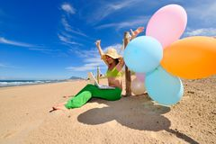 Young woman with colorful balloons using laptop Royalty Free Stock Photography