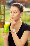 Young Woman with Colorful Cocktail Drink Outside Royalty Free Stock Image