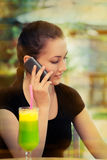 Young Woman with Colorful Cocktail Drink Talking on Her Phone Royalty Free Stock Image