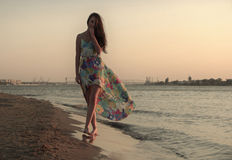 Young woman in a colorful dress on the ocean coast Royalty Free Stock Photography