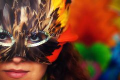 Young woman with a colorful feather carnival face mask on bright colorful background, eye contact, make up artist. Stock Photography
