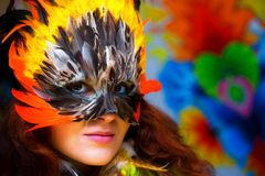 Young woman with a colorful feather carnival face mask on bright colorful background, eye contact, make up artist. Royalty Free Stock Photography