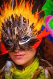 Young woman with a colorful feather carnival face mask on bright colorful background, eye contact, make up artist. Royalty Free Stock Image