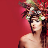 Young woman with colorful flowers in hair. Royalty Free Stock Photography