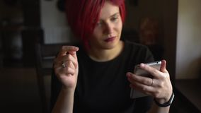 Young woman with colorful hair surfing internet on smartphone in cafe stock video