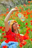 Young woman with colorful lollipop on field Stock Images