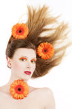 Young woman with colorful make-up and gerbera. Young woman with colorful make-up and a orange gerbera flowers in her hair Royalty Free Stock Image