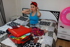 Young woman in colorful summer outfit near the red staffed suitcase. Young Girl packing suitcase on bed at home. Female with suitc Stock Image