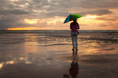 Young woman with colorful umbrella, standing on the beach Stock Image