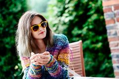 Young woman in colorful woolen sweater drinking coffee. Or tea on the terrace Royalty Free Stock Images