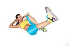 Young woman in colorfully sportswear doing exercise on white bac Stock Photos