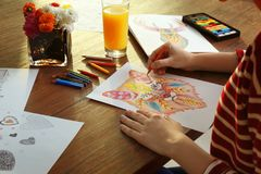 Young woman coloring pictures for adults. On table Stock Images