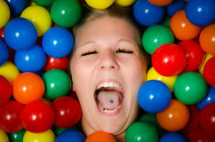 Young woman among colourful balls screaming. A young woman screaming loudly while covered with colored plastic balls Stock Image