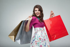 Young woman in colourful outfit. Studio portrait of a beautiful young woman, in a colourful outfit, holding in her hands a few shopping bags. she is laughing and Royalty Free Stock Images