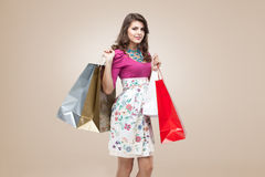 Young woman in colourful outfit. Studio portrait of a beautiful young woman, in a colourful outfit, holding in her hands a few shopping bags. she is laughing and Royalty Free Stock Image