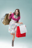 Young woman in colourful outfit. Studio portrait of a beautiful young woman, in a colourful outfit, holding in her hands a few shopping bags. she is hopping on Stock Images
