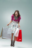 Young woman in colourful outfit holding bags Stock Photo