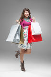 Young woman in colourful outfit holding bags. Studio portrait of a beautiful young woman, in a colourful outfit, holding in her hands a few shopping bags. she is Royalty Free Stock Photos