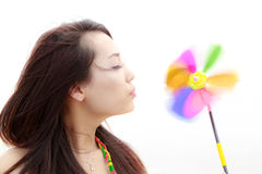 Young woman and colourful pinwheel Royalty Free Stock Photo