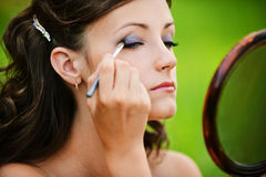 Young woman colouring her eyelids Stock Image
