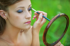 Young woman colouring her eyelids Royalty Free Stock Photography
