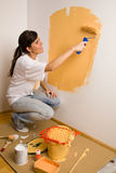 Young woman colours her flat
