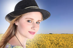Young woman with colza field in background Royalty Free Stock Photography