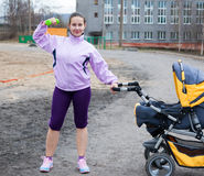 Young woman combines sport and a walk with baby Stock Photos