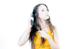 Young woman is combing. Young beautiful brown-haired woman is combing her hair Stock Photo
