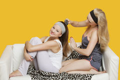 Young woman combing friend's hair while sitting on sofa over yellow background Stock Photos
