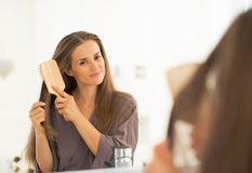 Young woman combing hair in bathroom Stock Image