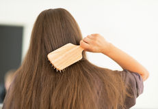 Young woman combing hair in bathroom. rear view Royalty Free Stock Images