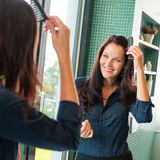 Young woman combing hair comb mirror bathroom. Morning preparation stock images